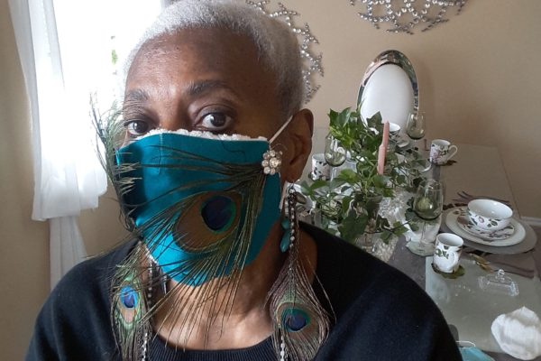 Nezzie Shabazz and her peacock mask with matching earrings.