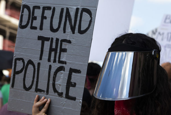 A protestor holds a sign calling for police defunding.