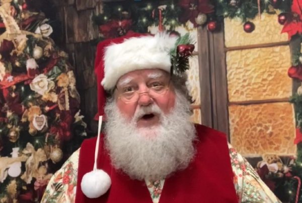 A man dressed as Santa Claus with Christmas decorations behind him