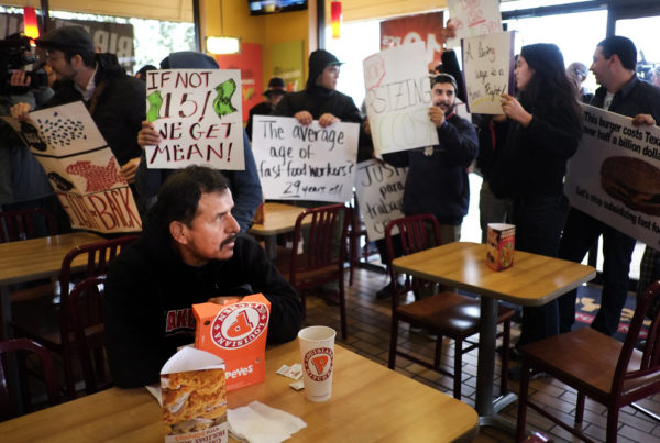 protesters for a $15 minimum wage hold up signs inside a fast food restaurant as a patron eating fried chicken looks on