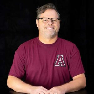 a portrait of a man in a maroon shirt