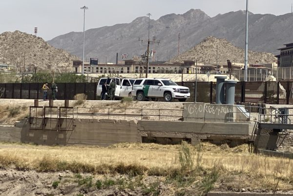 mountains at border in el paso with border patrol trucks and people in front of them