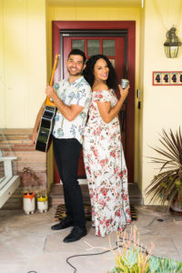 a man holds a guitar and a woman holds a microphone on a front porch