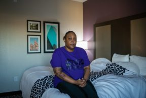 a woman in a purple shirt sitting on a hotel bed