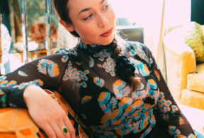 singer sarah jarosz sitting on a cough wearing a black top wtih a colorful print